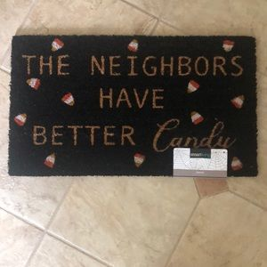 """The neighbors have better candy"" outdoor mat"